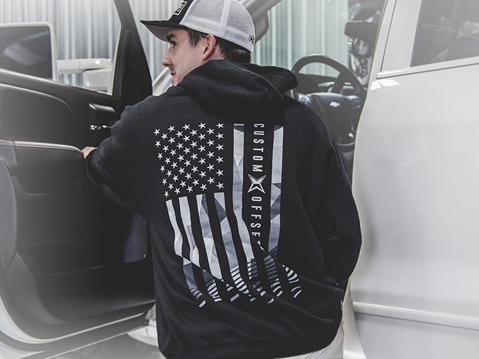 Male wearing a Custom Offsets flag sweatshirt and mesh hat getting into a truck