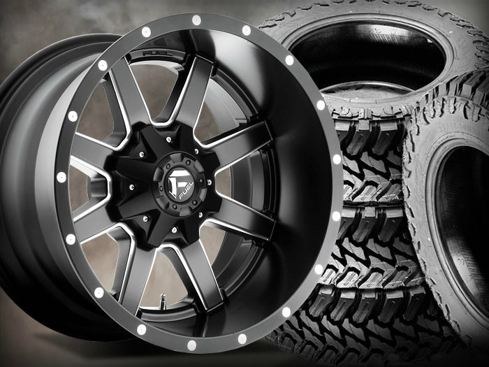 Black truck wheel with tires stacked behind